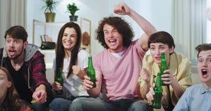 Voor de camera zeer charismatische close-up die op een voetbalwedstrijd letten terwijl het drinken van bier zijn zij zeer opgewek stock video