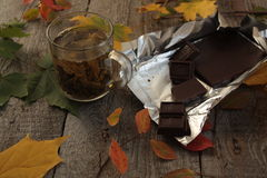 Voor de donkere houten lijst hete groene thee, chocolade, appelen, pruimen, framboos, boek de herfst of de winteravond Royalty-vrije Stock Afbeelding