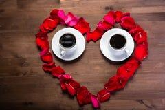 Voor de houten lijst, binnen het hart van de roze bloemblaadjes zijn twee koppen van koffie Royalty-vrije Stock Fotografie