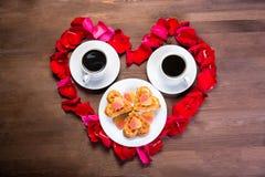 Voor de houten lijst, binnen het hart van de roze bloemblaadjes zijn twee koppen van koffie en een plaat met koekjes in de vorm v Royalty-vrije Stock Fotografie