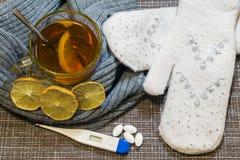 Voor de lijst, een glas thee met citroen in een grijze gebreide sjaal wordt verpakt die Ongeveer ligt hem vuisthandschoenen, pill stock afbeeldingen