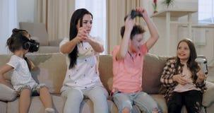 Voor de TV-moeder die met haar drie jonge geitjes tijd doorbrengen die samen aan PSP en andere het kleine meisje spelen spelen stock videobeelden
