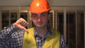 Voor een bouwwerf, zijn de ernstige arbeider of de ingenieur niet gelukkig makend een afkeergebaar stock videobeelden