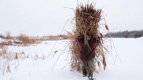 Voor een ijzige sneeuw de winterdag, draagt de dorpsbewoner droog die riet op zijn rug in een hooiberg over een snow-covered te v stock video