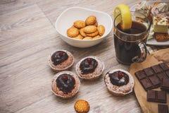 Voor een licht houten verfraaid tafelblad, vier chocolade-behandeld cupcakes, met rode bessen, zwarte die koffie, met een plak wo royalty-vrije stock afbeeldingen