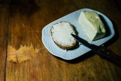 Voor een plaat, vet een stuk van brood met olie in stock afbeeldingen