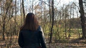 Voor een zonnige dag, loopt een portret van een mooi jong toeristenmeisje, maniervrouw, door het bos, de achtergrond van stock video