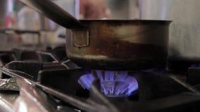 Voor het gasfornuis, op een vuurzee, is er een vuile gietlepel met een handvat stock videobeelden