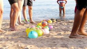 Voor het strand, op het zand zijn ballons met water in plaats van lucht worden gevuld die mensen die een rust speelpretspelen op  stock video