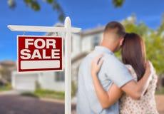 Voor het Teken van Verkoopreal estate, Militair Paar die Huis bekijken Stock Afbeelding