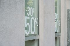 Voor het winkelvenster, glas, geschreven kortingen van vijftig percenten en dertig percenten zwarte vrijdag, Kerstmiskortingen, n stock foto