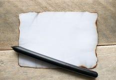 Voor houten raad, is er een zwarte pen, een wit blad dat van document dat bij de randen wordt gebrand, ruimte voor tekst verlaat stock afbeeldingen