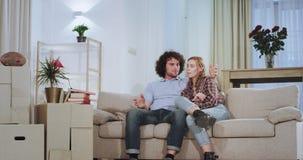 Voor TV op het bank charismatische paar die van de tijd in een nieuw huisflat zij genieten het gelukkige opstaan van stock videobeelden
