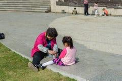 Voor vakantie, spelen de oude mensen en de kinderen met stenen dichtbij het parkgazon Royalty-vrije Stock Foto's