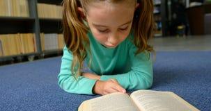 Vooraanzicht van aandachtig Kaukasisch schoolmeisje die een boek in bibliotheek lezen op school 4k stock footage