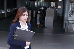 Vooraanzicht van aantrekkelijke jonge Aziatische bedrijfsvrouw die met ringsbindmiddel omhoog de treden lopen bij ingang van stat Royalty-vrije Stock Afbeeldingen
