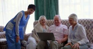Vooraanzicht van actieve Kaukasische hogere vrienden en vrouwelijke arts die laptop in het verpleeghuis 4k met behulp van stock videobeelden