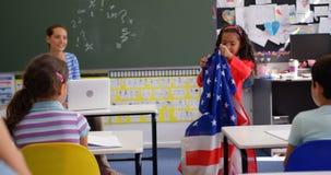 Vooraanzicht van Afrikaans Amerikaans schoolmeisje die over Amerikaanse vlag in het klaslokaal 4k verklaren stock video