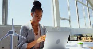 Vooraanzicht van Afrikaanse Amerikaanse Onderneemster die laptop met behulp van bij bureau in een modern bureau 4k stock footage