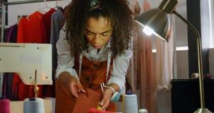 Vooraanzicht van Afrikaanse Amerikaanse vrouwelijke manierontwerper die doeksteekproeven bekijken in workshop 4k stock video