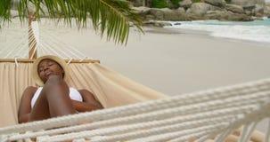 Vooraanzicht van Afrikaanse Amerikaanse vrouwenslaap in een hangmat op het strand 4k stock videobeelden