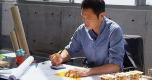 Vooraanzicht van Aziatische mannelijke architect die aan blauwdruk bij bureau in een modern bureau 4k werken stock footage