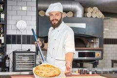 Vooraanzicht van bakker die chef-kok` s uniformjas dragen en pizza op metaalschop houden royalty-vrije stock foto