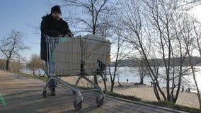 Vooraanzicht van dakloze rijpe mensen duwende kar stock video