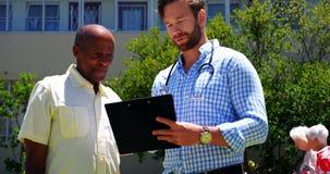 Vooraanzicht van de actieve Afrikaanse Amerikaanse hogere mens en mannelijke arts die over medisch rapport in t bespreken stock videobeelden