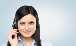 Vooraanzicht van de glimlachende donkerbruine exploitant van de steuntelefoon met hoofdtelefoon royalty-vrije stock foto