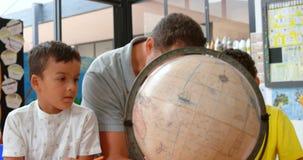 Vooraanzicht van de jonge Kaukasische mannelijke jonge geitjes van het leraarsonderwijs over aardrijkskunde met bol in klaslokaal stock video