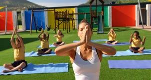 Vooraanzicht van de vrouwelijke schoolkinderen van het leraarsonderwijs om yoga in de schoolspeelplaats 4k uit te voeren stock video