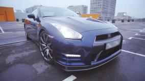 Vooraanzicht van donkerblauwe nieuwe autotribune op leeg parkeren presentatie koplampen auto Koude schaduwen stock footage