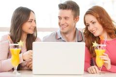 Vooraanzicht van drie studenten die laptop met behulp van Stock Afbeelding