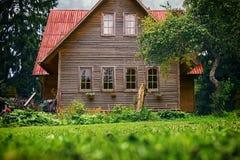 Vooraanzicht van een huis in de voorsteden met rood dak en groene tuin in de zomertijd stock afbeeldingen