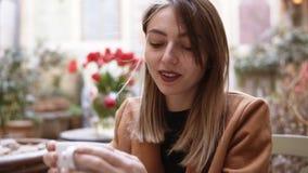 Vooraanzicht van een mooi wijfje die omhoog in plezier, het drinken smakelijke koffie in koffie kijken Het aantrekkelijke jonge v stock video