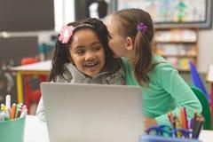 Vooraanzicht van een schoolmeisje die een geheim fluisteren in vriendenoor terwijl haar vriend die in classroo lachen stock fotografie