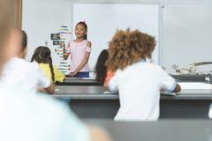 Vooraanzicht van een schoolmeisje die met zijn klasgenoten over DNA-structuurmodel interactie aangaan royalty-vrije stock foto's
