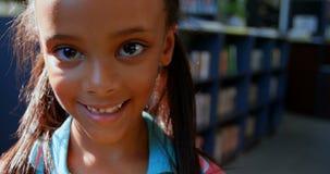 Vooraanzicht van gelukkig Afrikaans Amerikaans schoolmeisje dat zich in bibliotheek op school 4k bevindt stock video