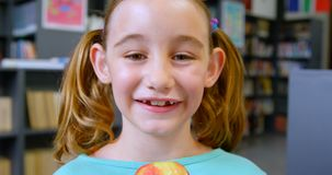 Vooraanzicht van gelukkig Kaukasisch schoolmeisje die zich in bibliotheek op school 4k bevinden stock footage