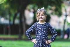 Vooraanzicht van gelukkig meisje in kleding die zich in het park bevinden royalty-vrije stock fotografie