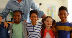 Vooraanzicht van gelukkige multi-etnische schoolkinderen met Kaukasische mannelijke leraar die zich in klaslokaal bevinden stock videobeelden
