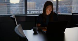 Vooraanzicht van het aandachtige jonge Kaukasische vrouwelijke uitvoerende werken aan laptop n modern bureau 4k stock footage