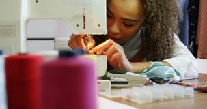 Vooraanzicht van het Afrikaanse Amerikaanse vrouwelijke manierontwerper werken met naaimachine in workshop 4k stock footage