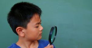 Vooraanzicht van het Aziatische schooljongen bekijken door vergrootglas in klaslokaal school 4k stock footage