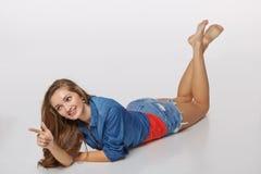 Vooraanzicht van het glimlachen het mooie vrouw liggen op de vloer over gr. Stock Foto's