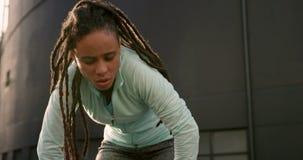 Vooraanzicht van het jonge Afrikaanse Amerikaanse vrouw rusten na het uitoefenen in de stad 4k stock video