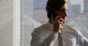 Vooraanzicht van het jonge Kaukasische mannelijke uitvoerende spreken op mobiele telefoon in een modern bureau 4k stock footage