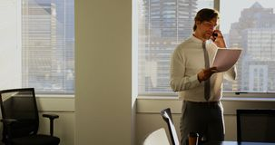 Vooraanzicht van het jonge Kaukasische mannelijke uitvoerende spreken op mobiele telefoon in een modern bureau 4k stock videobeelden