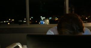 Vooraanzicht van het vermoeide jonge Kaukasische mannelijke uitvoerende werken aan computer bij bureau in modern bureau 4k stock footage